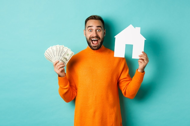 Real estate concept and mortgage concept. excited man showing dollars and paper maket of house