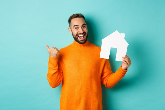 Real estate concept. satisfied man recommending agency, pointing at copy space banner with thumb, showing paper house maket.
