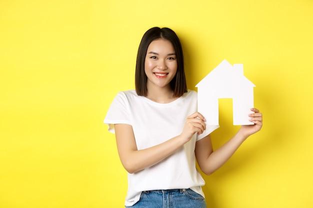 不動産のコンセプト。紙の家の切り抜きを表示し、カメラを見て、プロパティを購入し、黄色の背景の上に立って笑顔の美しい女性。
