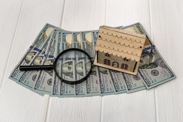 달러와 목조 주택 모델 부동산 개념