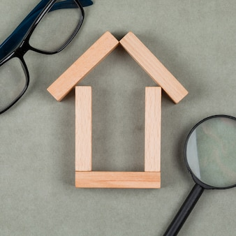 Real estate concept with house made of wooden blocks, glasses, magnifying glass on grey background close-up.