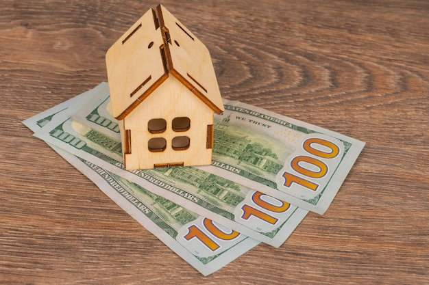 Real estate concept with wooden house model and 100 dollar banknotes