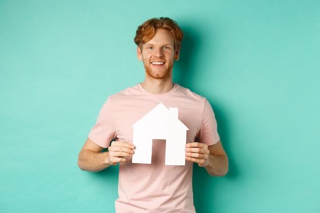부동산 개념. 빨간 머리를 가진 젊은 남자, t- 셔츠를 입고, 종이 집 컷 아웃을 표시 하 고 민트 배경 위에 서 행복 하 게 웃 고. 공간 복사