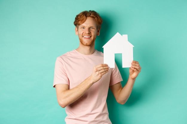 부동산 개념. 빨간 머리를 가진 젊은 남자, t- 셔츠를 입고, 종이 집 컷 아웃을 표시 하 고 민트 배경 위에 서 행복 하 게 웃 고.