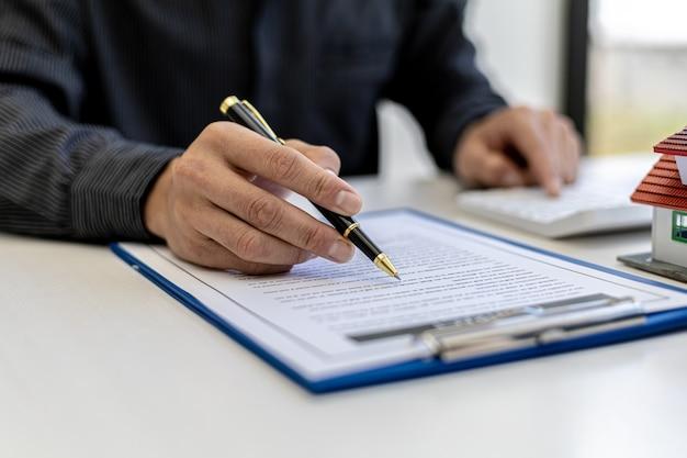 Концепция договора о недвижимости. покупатель подписывает с продавцом договор купли-продажи дома. продавец рассчитывает стоимость покупки дома и объясняет детали контракта.