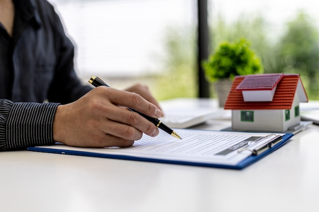 Real estate contract agreement concept. buyer is signing house purchase contract with seller. salesperson calculates house purchase cost and explains details on contract.