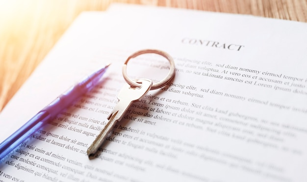 Real estate contract with keys and pen for signing