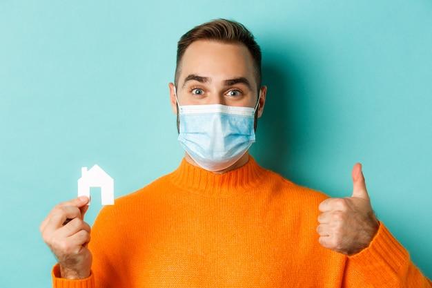 Concetto di pandemia immobiliare e coronavirus. primo piano dell'uomo adulto nella mascherina medica che tiene piccola casa