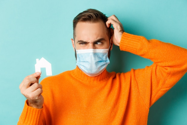 Real estate and coronavirus pandemic concept. confused man in face mask scartching head while looking at small paper house, wearing orange sweater near light blue studio background.
