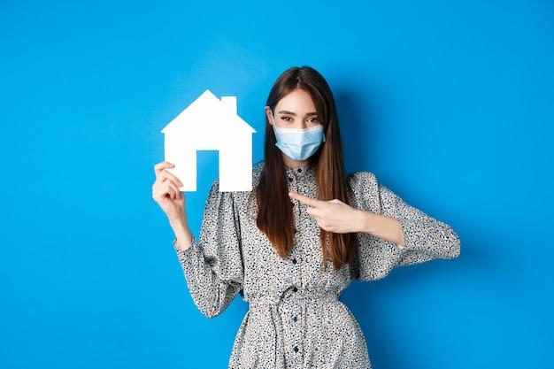부동산, covid-19 및 유행성 개념. 파란색에 서 종이 집 컷 아웃에서 가리키는 의료 마스크에 웃는 여성 모델.