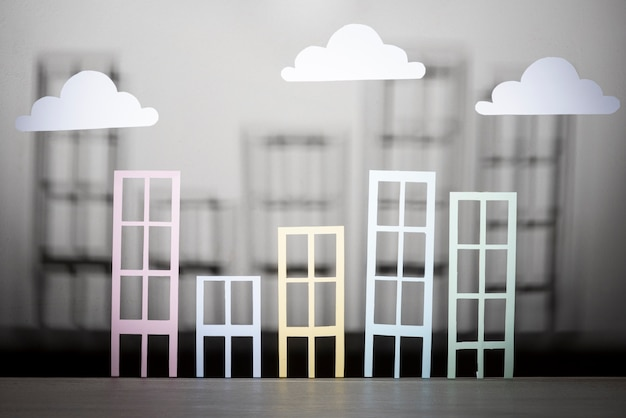 Real estate design with paper buildings and clouds