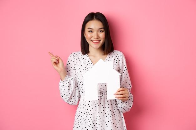 Недвижимость. возбужденная азиатская женщина показывает модель бумажного дома, указывая влево на копировальное пространство, стоя над розовым