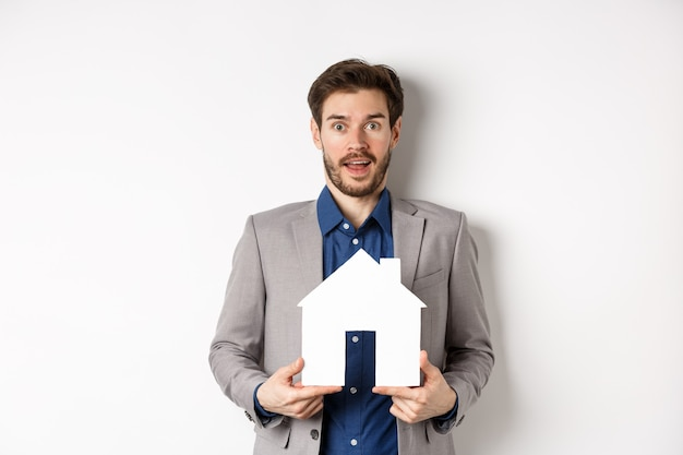 Недвижимость. взволнованный деловой человек в костюме держит вырез из бумажного домика и смотрит прямо