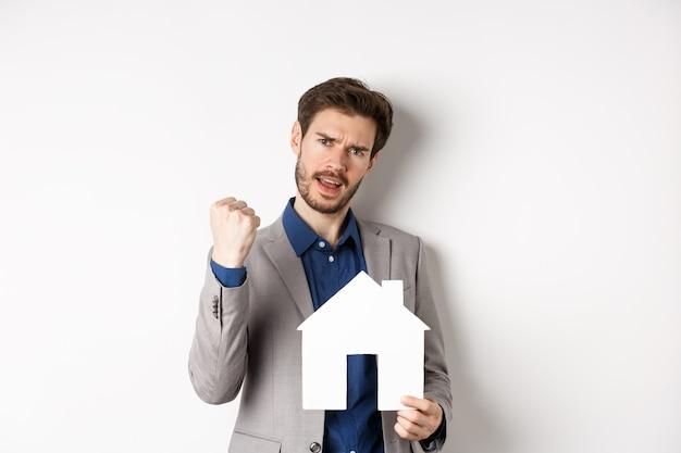 Недвижимость. возбужденный мужчина покупает дом и показывает бумажный вырез дома, говорит «да» и с радостью нагнетает кулак, стоя в костюме на белом фоне.