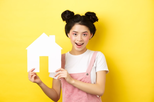 Real estate and family concept. cute asian woman with bright makeup and stylish hairbuns, showing paper house cutout, smiling determined, yellow