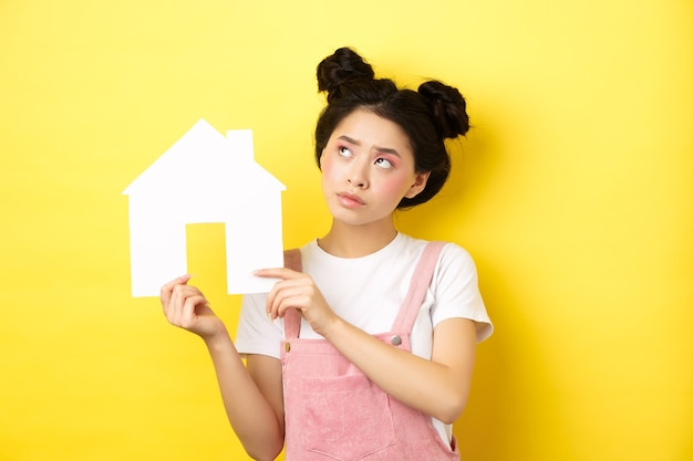 Real estate and family concept. thoughtful asian girl dream of house, showing paper home cutout and look at upper left corner pensive, yellow