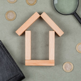 Real estate and financial concept with wooden blocks, magnifying glass, notebook, coins on grey background close-up.