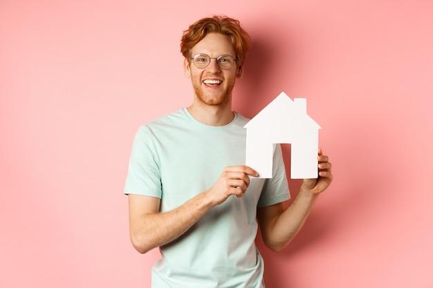 不動産。ピンクの背景の上に立って、紙の家の切り抜きと笑顔を見せて、tシャツとメガネのハンサムな赤毛の男。