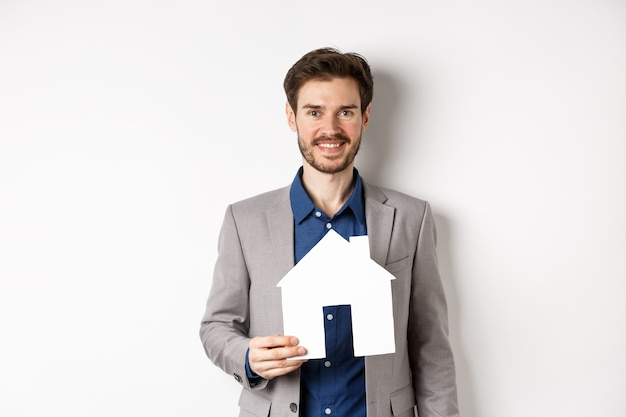 Real estate. handsome young businessman buying property, holding paper house cutout and smiling, agency advertisement, white background.