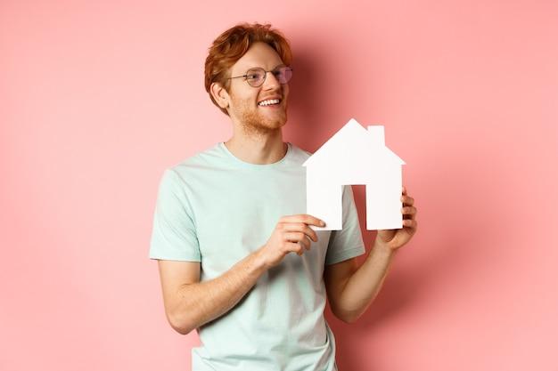 不動産。ピンクの背景の上に立って、プロパティを購入し、右を見て、紙の家の切り抜きを表示することを夢見て幸せな赤毛の男。