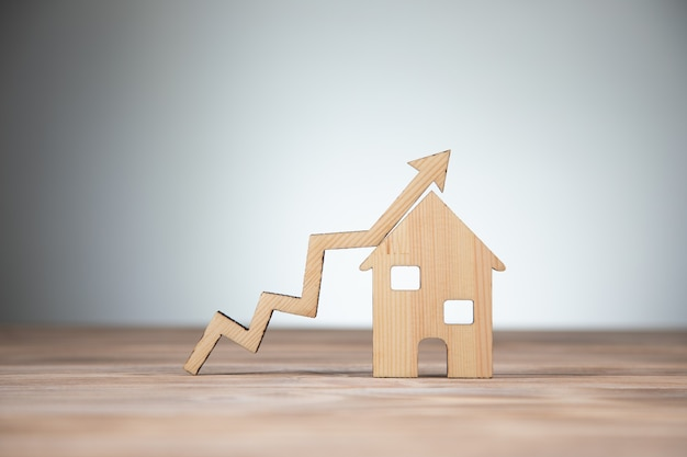 Real estate, home model and arrow graph