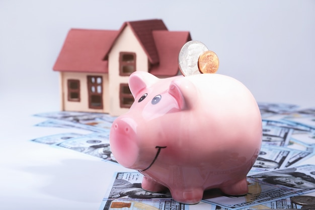 Real estate or home saving. piggy bank with coins on blur background money and house.