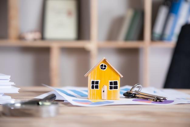 Недвижимость, модель дома с ключом на графике