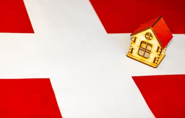 스위스의 부동산 스위스 국기에 목조 주택입니다. 부동산, 임대 또는 모기지 개념입니다.