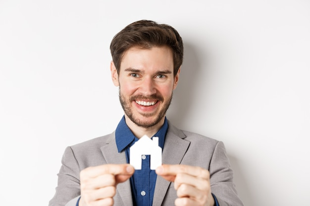 Real estate and insurance concept. handsome man in suit smiling, showing small paper house cutout, standing on white background.