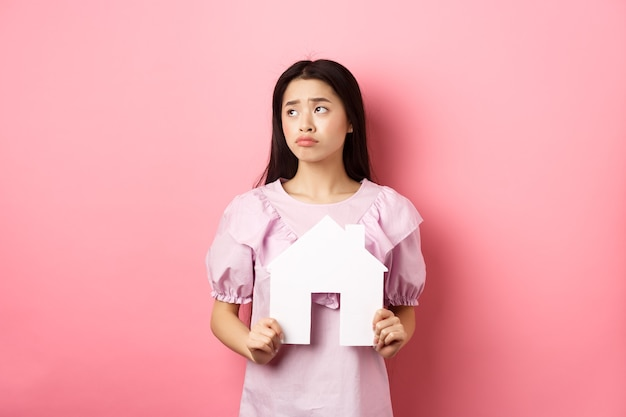 Real estate and insurance concept. sad asian woman looking aside with unfair face, showing paper house cutout, dreaming of apartment, standing against pink background.