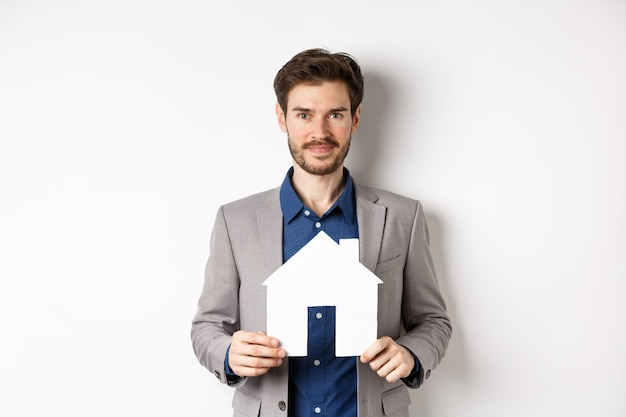 Real estate and insurance concept. salesman in grey suit showing paper house cutout, selling property, smiling friendly at camera, white background.
