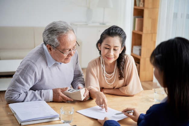 Real estate manager explaining senior couple how to fill sale deed form