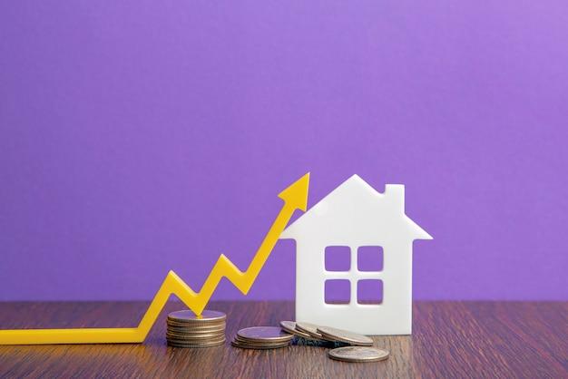 부동산 시장, 그래프, 위쪽 화살표. 주택 건설 모델과 동전 더미. 인플레이션, 경제 성장, 보험 서비스 가격의 개념. 복사 공간