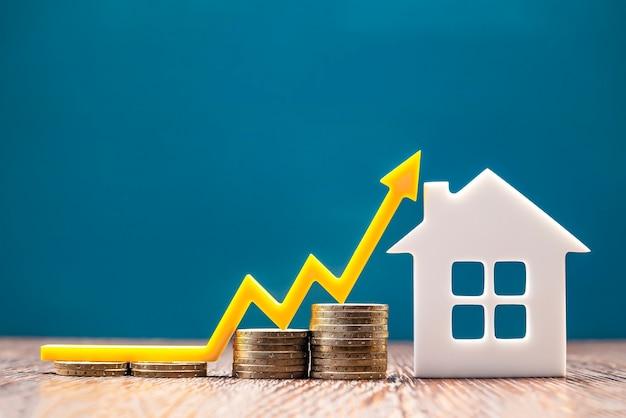 부동산 시장, 그래프, 위쪽 화살표. 집 모델과 동전 더미입니다. 인플레이션, 경제 성장, 보험 서비스 가격의 개념. 복사 공간