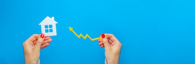 부동산 시장, 그래프, 위쪽 화살표입니다. 주택 가격 상승. 손에 집 모델입니다. 인플레이션, 경제 성장, 보험 서비스 및 부동산 가격의 개념.