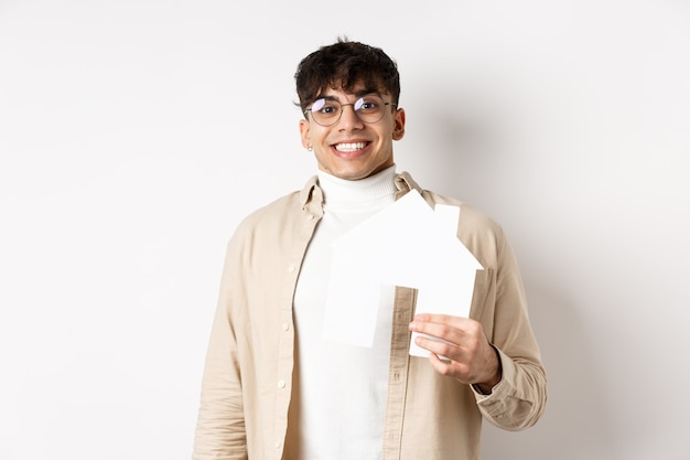 Real estate and mortgage concept. cheerful young guy renting apartment, showing paper house cutout and smiling happy, buying property, white wall.