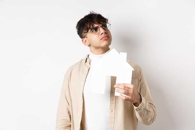 Real estate and mortgage concept. pensive young man thinking of new apartment, holding paper house cutout and look at upper right corner logo, standing on white wall.