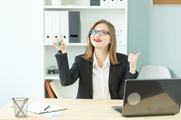 Real estate, new home and business people concept - happy realtor woman giving you keys and showing thumb up