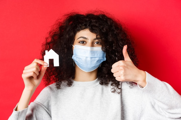 Real estate and pandemic concept. close-up of woman recommending agency, wearing medical mask, showing thumbs up and paper house cutout, red wall.