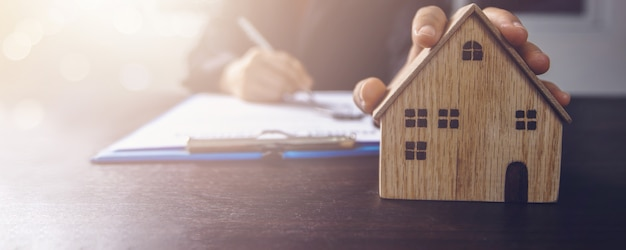 Real estate, property and home owner signing contract concept, small wooden house model on office table with hand of woman buyer sign on rental agreement paper to rent above  mentioned residence