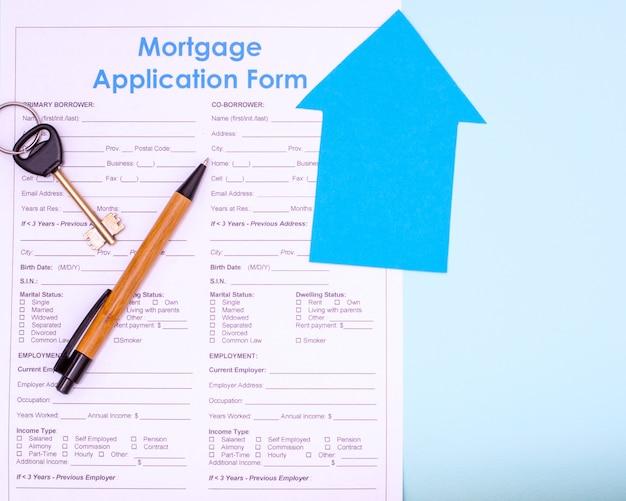 부동산 구매, 모기지 개념입니다. 평평한 모기지 신청서, 펜 및 파란색 배경의 미래 집이나 아파트 열쇠, 위쪽 전망, 복사 공간