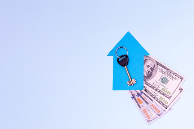 Real estate purchase, mortgage, rental concept. the key to a new apartment or house lies on a small blue paper house on a fan of 100 dollar bills on a blue background, copy space, flat lay, top view