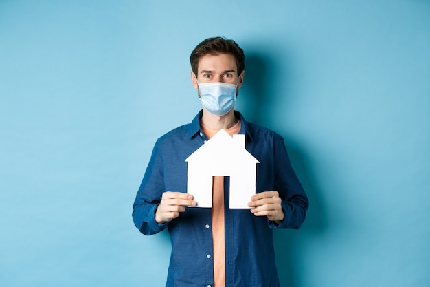 Real estate and quarantine concept. happy young man in medical mask showing house cutout, buying property, standing on blue background.