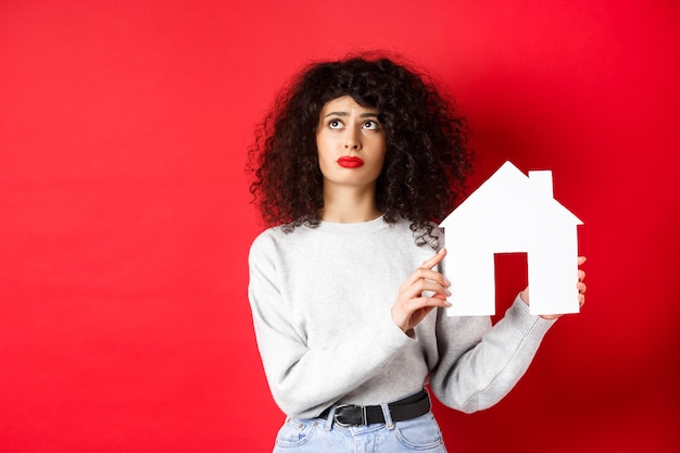 Real estate. sad woman thinking of buying own house, showing paper home cutout and looking up with uspet face, standing on red wall.