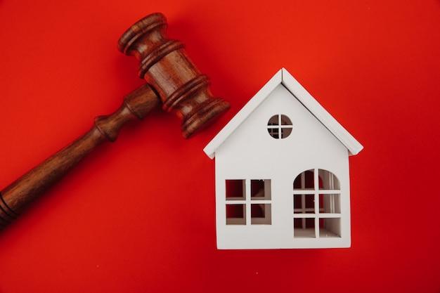Концепция аукциона продажи недвижимости - модель молотка и дома на красном фоне.