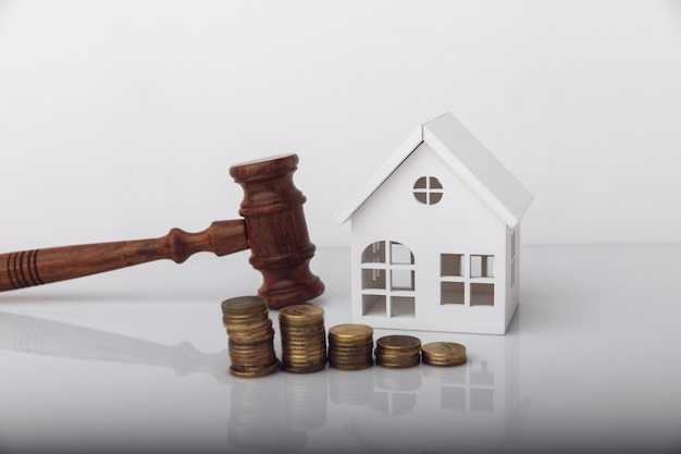 Real estate sale auction concept wooden gavel and house model with coins