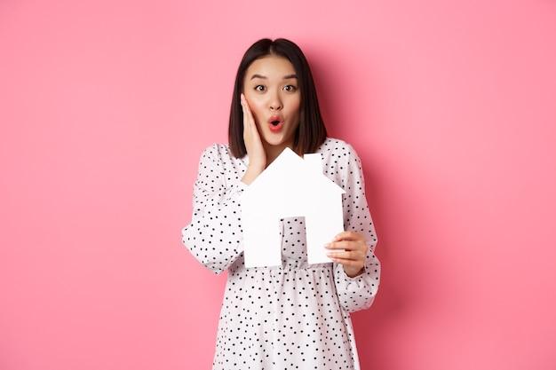 Недвижимость. удивленная и изумленная азиатская женщина смотрит в камеру, говорит вау и показывает модель бумажного дома, стоящую над розовым