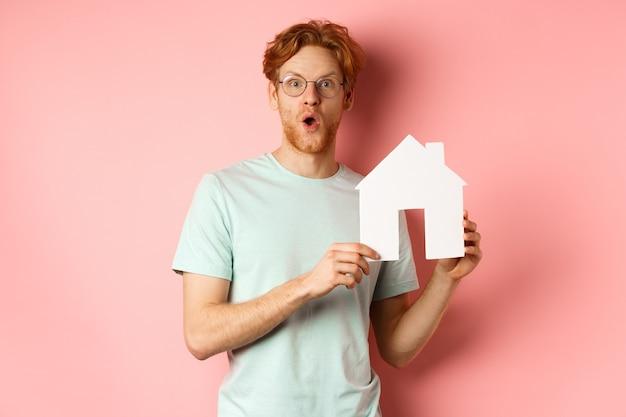 不動産。赤い髪とあごひげを生やし、眼鏡とtシャツを着て、紙の家の切り抜きを見せて、ピンクの背景の上に立って、すごいと言って感動した様子で驚いた若い男。