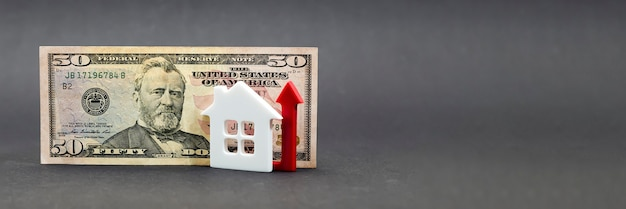 Real estate value growth. real estate market, home insurance, mortgage interest rise, fifty dollar bill on black background. copy space