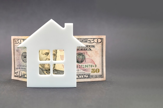 Real estate value growth. real estate market, home insurance, mortgage interest rise, fifty dollar bill on black background, white house and an arrow pointing up.